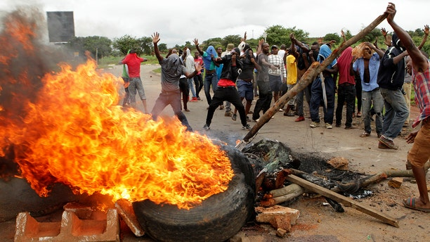"""In this Tuesday, Jan. 15, 2019 file photo, protestors gather near a burning tire during a demonstration over the hike in fuel prices in Harare, Zimbabwe. 2019 is already a busy year for internet shutdowns in Africa, with governments ordering cutoffs as soon as a crisis appears. Zimbabwe ordered a """"total internet shutdown"""" in recent days during protests over a dramatic fuel price increase and a resulting deadly crackdown."""