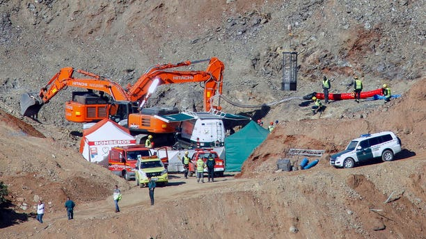 In this photo taken on Thursday, Jan. 24, 2019, drill and excavating machinery work on top of the mountain next to a deep borehole to reach a 2-year-old boy trapped there for twelve days near the town of Totalan in Malaga, Spain.
