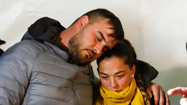 In this photo taken on Thursday, Jan. 24, Jose Rosello and Victoria Garcia, parents of 2-year-old boy trapped in a deep borehole, take part in a vigil at the town of Totalan near Malaga, Spain. Spanish authorities say that rescue experts are using explosives to make their way through a wall of hard rock to reach the space where a three-year-old boy has been trapped for 12 days.