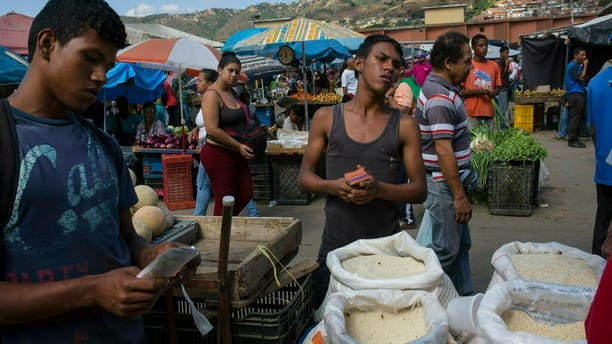 Workers waiting for customers at their vegetable stand at a wholesale food market in Caracas on Monday. (AP Photo/Rodrigo Abd)