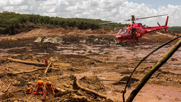 29 January 2019, Brazil, Brumadinho: Firefighters recover a body with the help of a helicopter. Helpers search the mud for victims and possible survivors. The dams of a retention basin at the Córrego do Feijão iron ore mine were broken on Friday (25.01.2019). A mudslide rolled over the site and nearby settlements, killing many people. Photo: Rodney Costa/dpa (Getty Images)