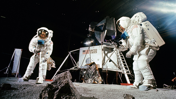 Buzz Aldrin, on the left, practices scooping up a sample while Neil Armstrong, on the right, photographs the collection, during a practice session held before the Apollo 11 mission.