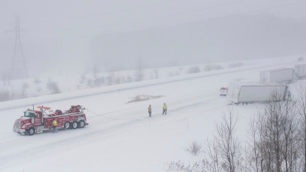 A Merl's Towing Service truck pulls a semi-trailer truck out of the snow along M-6 near exit 1 near Grandville on Wednesday, Jan. 30, 2019. Subzero temperatures were recorded across the area.