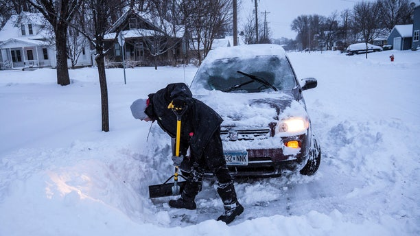 Adam Fischer shovels out his vehicle to go to work Monday, Jan. 28, 2019, in Rochester, Minn.