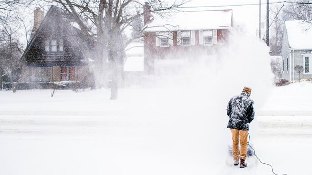 Stephen Johnson clears snow off his neighbor's driveway into Court Street during a winter snowstorm on Monday, Jan. 28, 2019, in Flint, Mich.