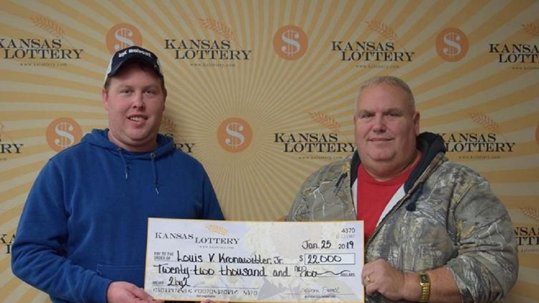 Kansas Lottery winner Louis V. Kronawitter Jr., right, and his son Austin Kronawitter pose with a $22,000 check. (Kansas Lottery)