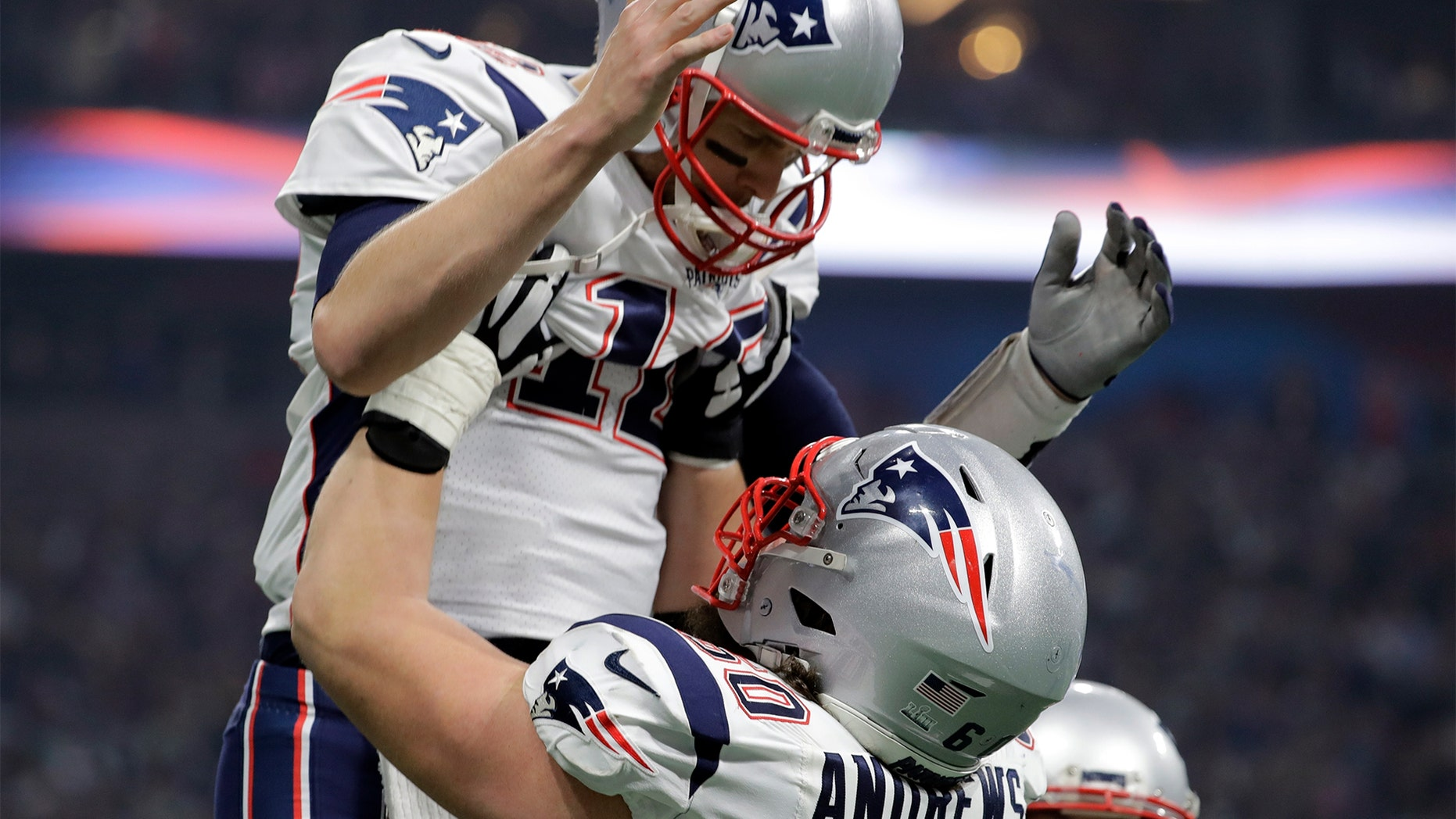 New England Patriots' David Andrews (60) picks up Tom Brady (12) after the Patriots scored a touchdown during the second half of the NFL Super Bowl VII against the Los Angeles Rams Sunday in Atlanta. (AP Photo/Jeff Roberson)