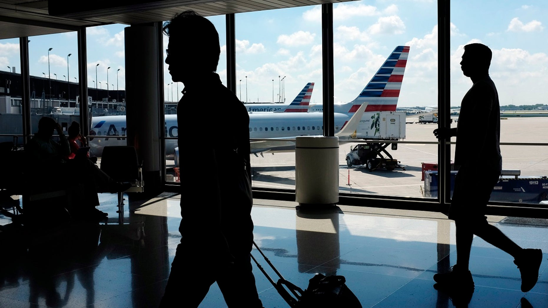 """FILE: Passengers go to their gates through the terminal when American Airlines flights are waiting to travel to the Hare International Airport in Chicago on August 1<div class=""""e3lan e3lan-in-post1""""><script async src=""""//pagead2.googlesyndication.com/pagead/js/adsbygoogle.js""""></script> <!-- Text_Display_Responsive --> <ins class=""""adsbygoogle""""      style=""""display:block""""      data-ad-client=""""ca-pub-6192903739091894""""      data-ad-slot=""""3136787391""""      data-ad-format=""""auto""""      data-full-width-responsive=""""true""""></ins> <script> (adsbygoogle = window.adsbygoogle    []).push({}); </script></div>, 2016."""