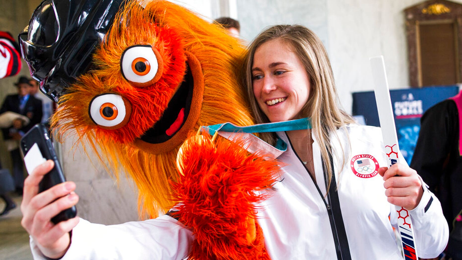 Olympic gold medalist hockey player Haley Skarupa talks a selfie with the NHL Philadelphia Flyers mascot Gritty.