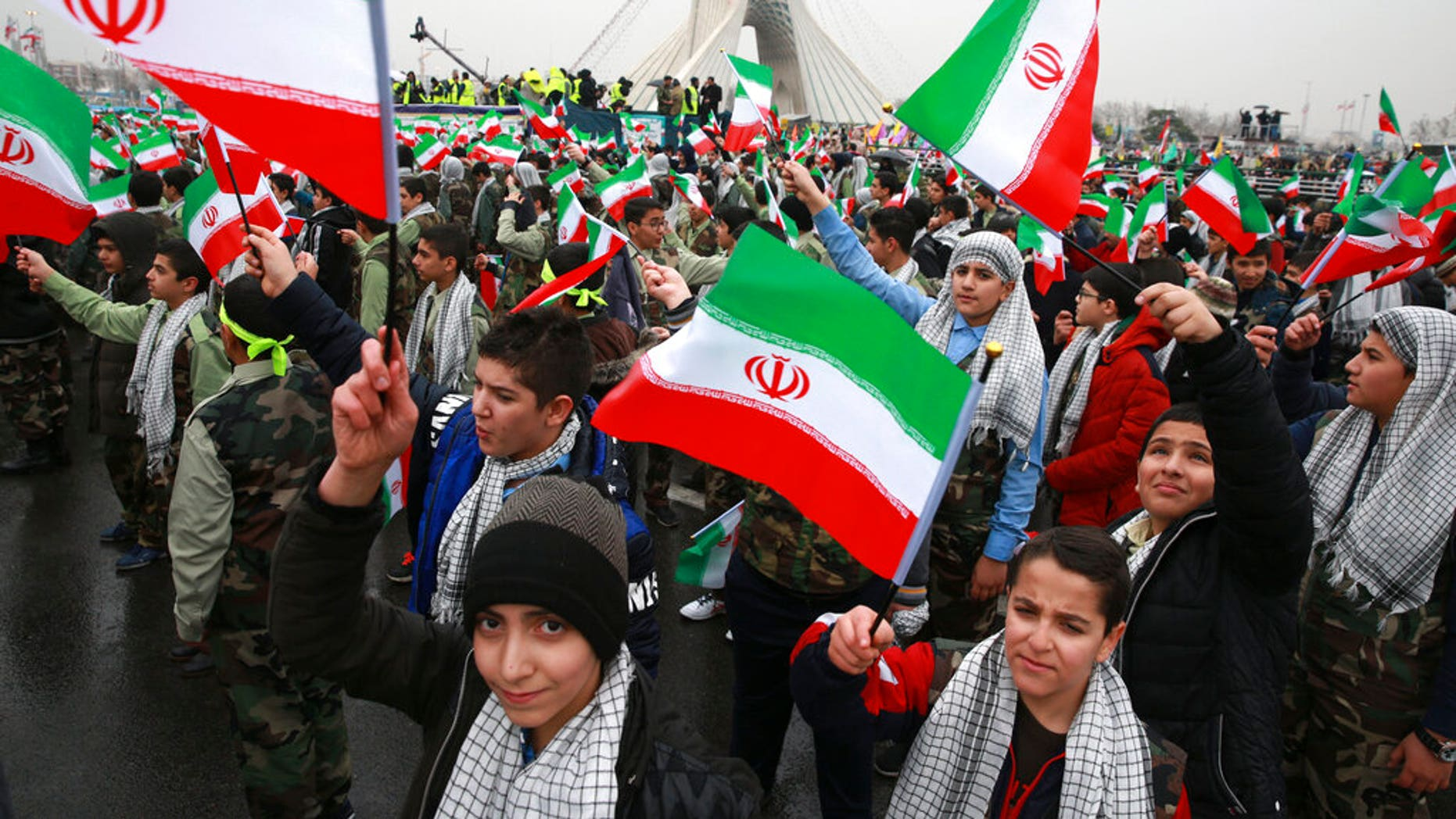 Children wave Iranian flags during a ceremony celebrating the 40th anniversary of the Islamic Revolution at the Azadi Freedom Square in Tehran Iran Monday Feb. 11 2019. Hundreds of thousands of people poured out onto the streets of Tehran and other