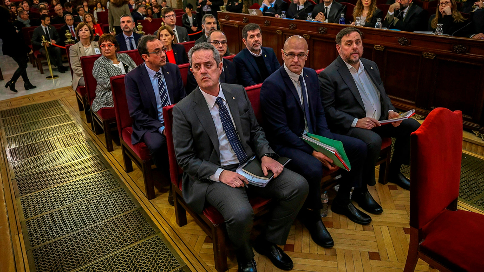 Front row from left, Joaquim Form, Raul Romeva, Oriol Junquera, second row from left, Josep Rull, Jordi Turull, Jordi Sanchez, third row from left, Dolors Bassa, Carmen Forcadell, Jordi Cuixart, back row from left, Meritxell Borras, Santiago Vila, and Carles Mundo during the trial at the Spanish Supreme Court in Madrid, Tuesday, Feb. 12.