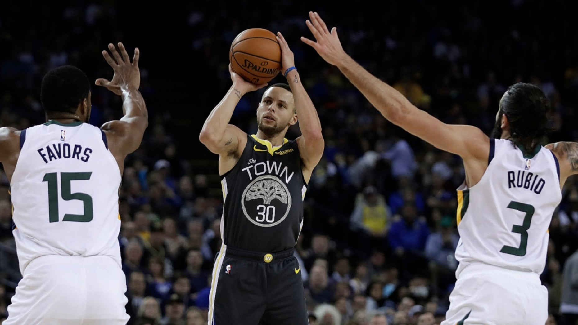 Golden State Warriors' Stephen Curry, center, shoots between Utah Jazz's Derrick Favors (15) and Ricky Rubio (3) during the second half of an NBA basketball game Tuesday, Feb. 12, 2019, in Oakland, Calif. (Associated Press)