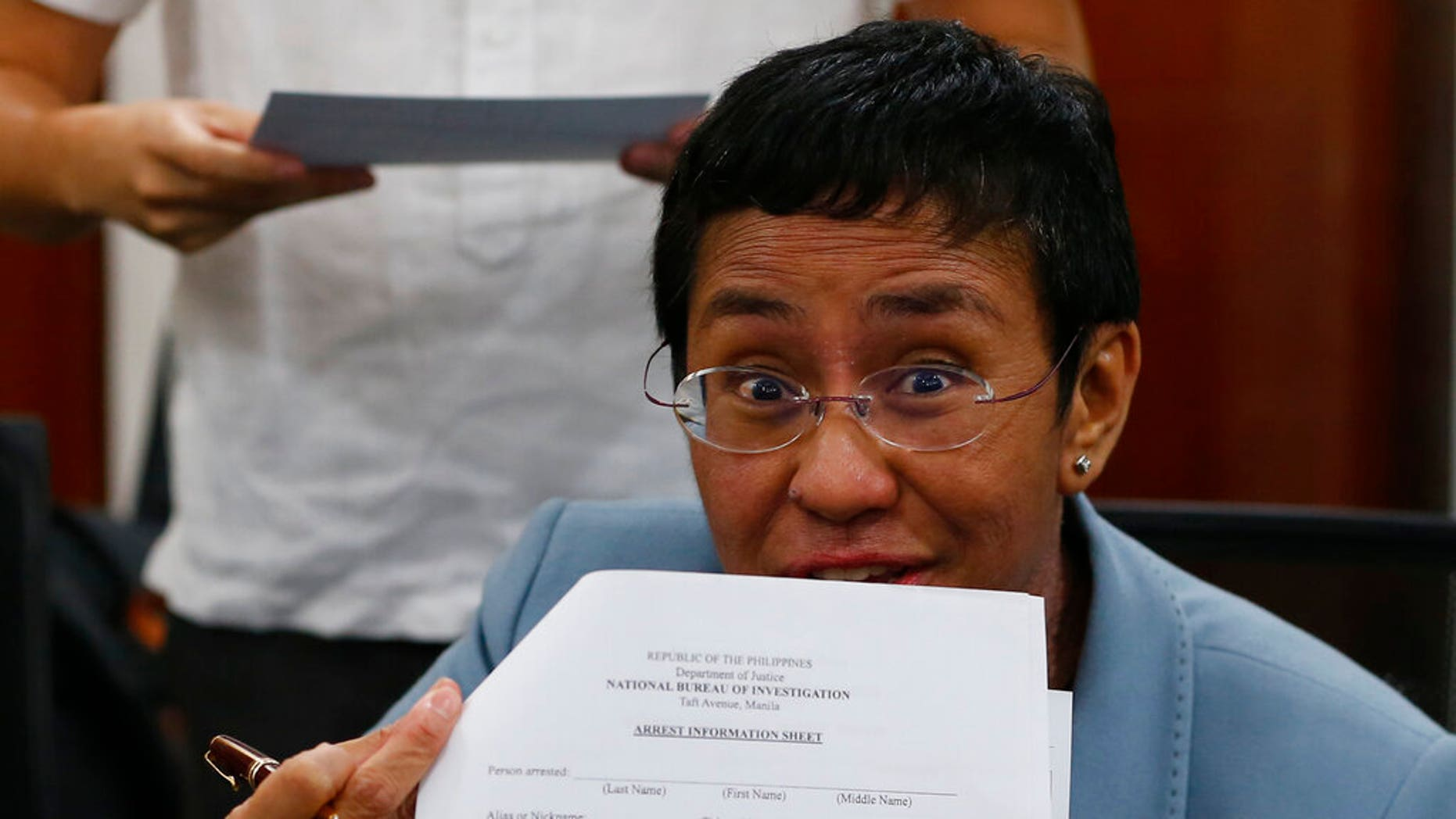 Maria Ressa, the award-winning head of a Philippine online news site Rappler that has aggressively covered President Rodrigo Duterte's policies, shows an arrest form after being arrested by National Bureau of Investigation agents in a libel case Wednesday, Feb. 13, 2019, in Manila, Philippines.