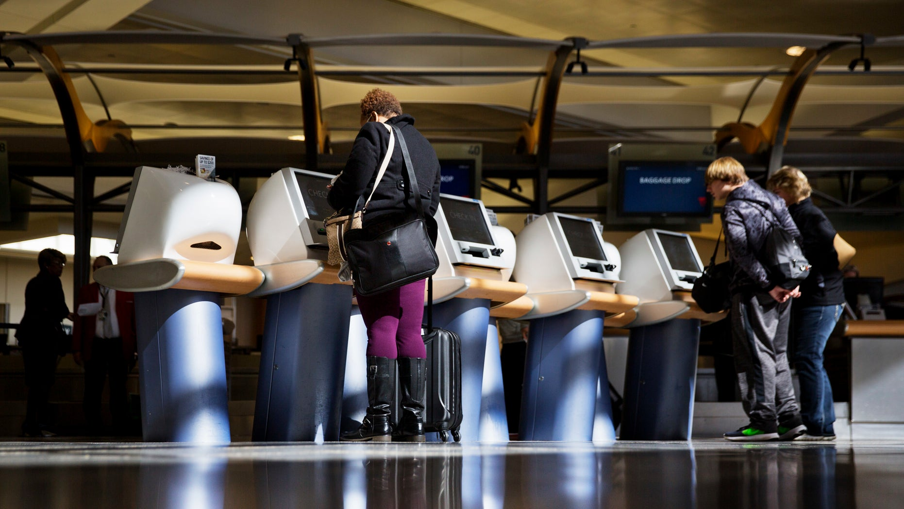In this 2017 file, passengers are registered on Delta Air Lines at airport booths. Major American airlines say they will soon change their ticket sales process to give passengers the opportunity to identify themselves as men or women.
