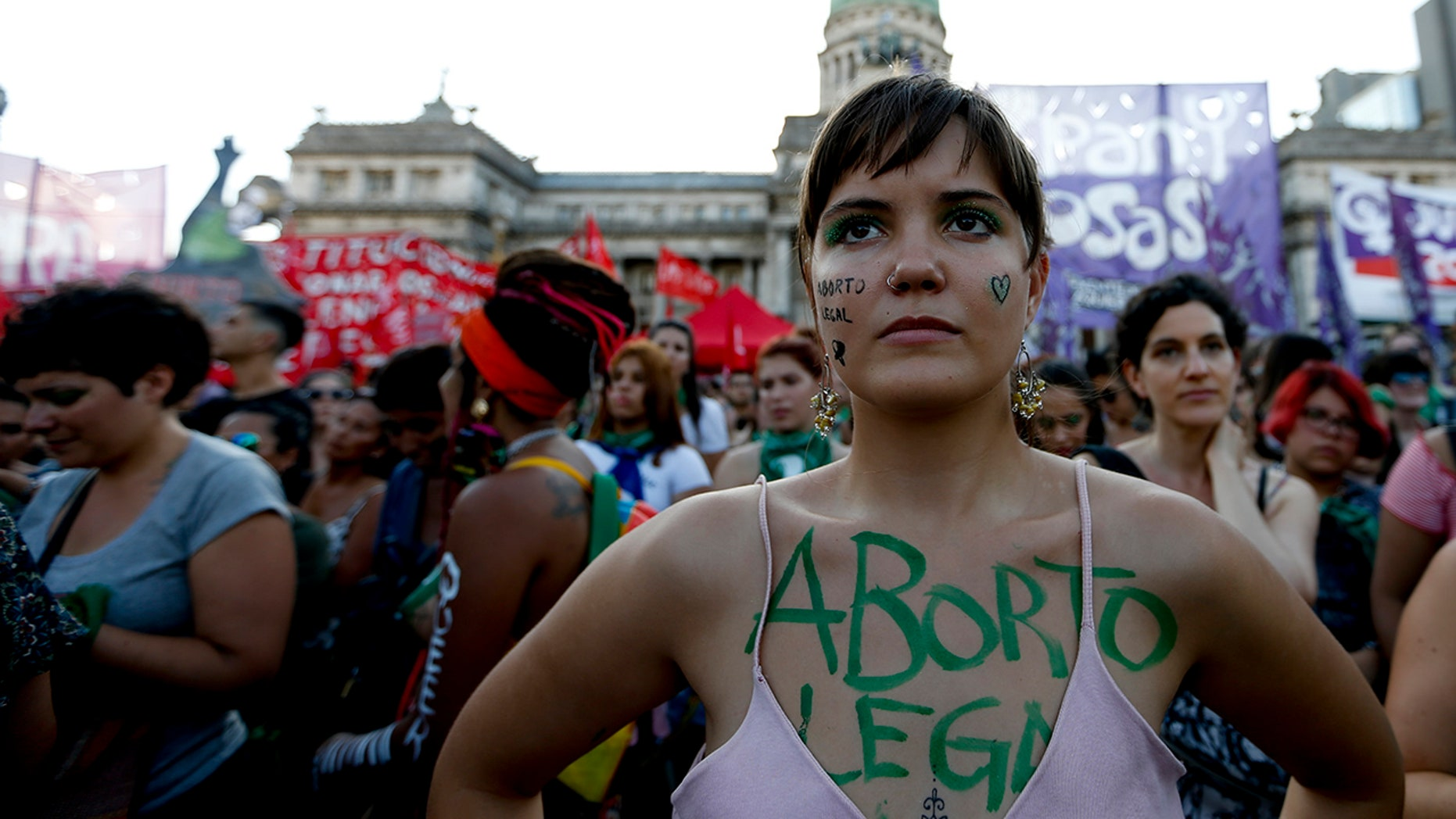 """A woman covered by the Spanish words """"Legal abortion"""" attends a pro-choice rally in favor of decriminalizing abortion outside Congress in Buenos Aires, Argentina, Tuesday, Feb. 19."""