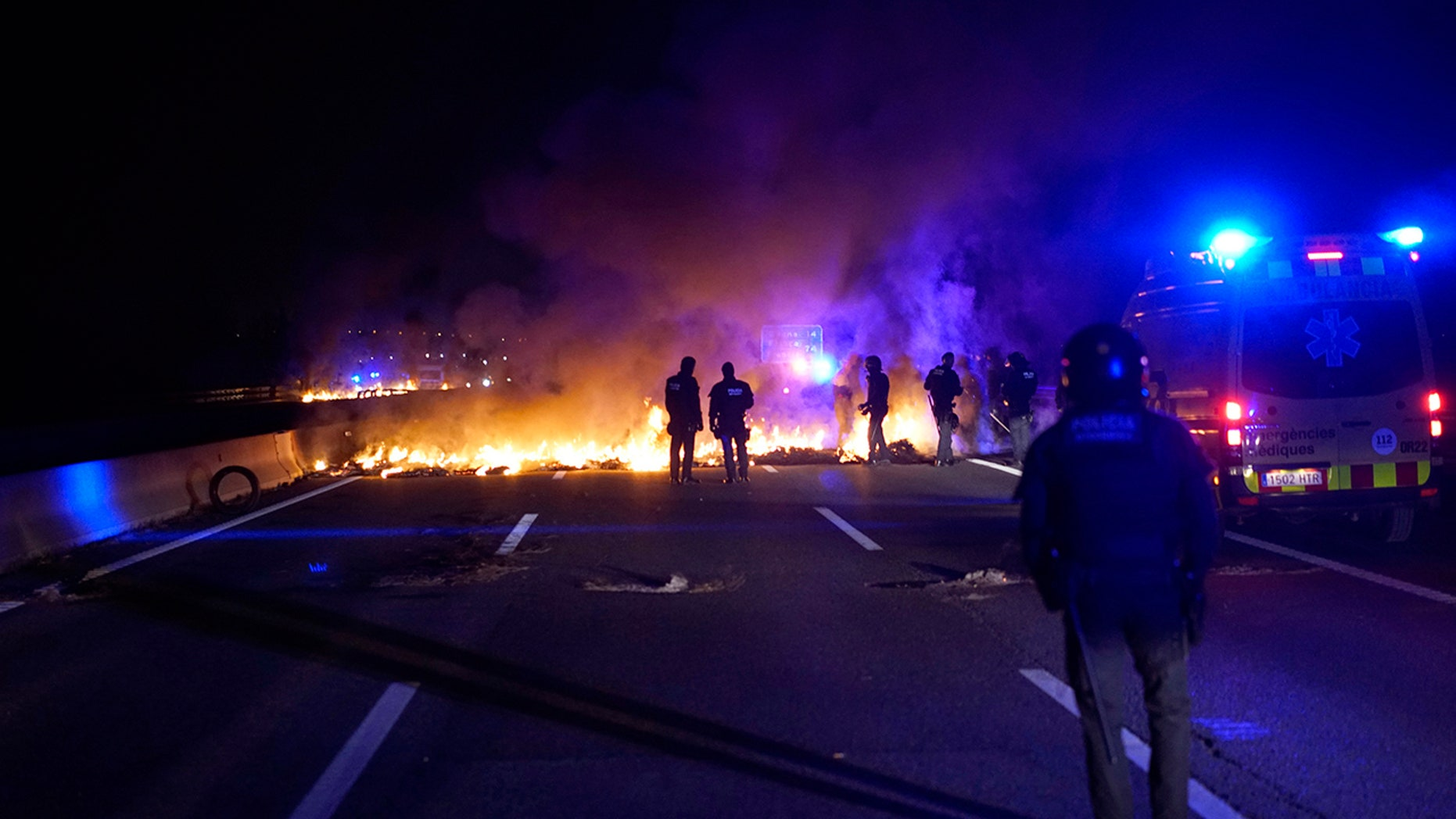 Police officers try to remove burning tires, set by demonstrators to block a highway in protest of the imprisonment of pro-independence political leaders during a general strike in Catalonia, Spain, Thursday, Feb. 21.