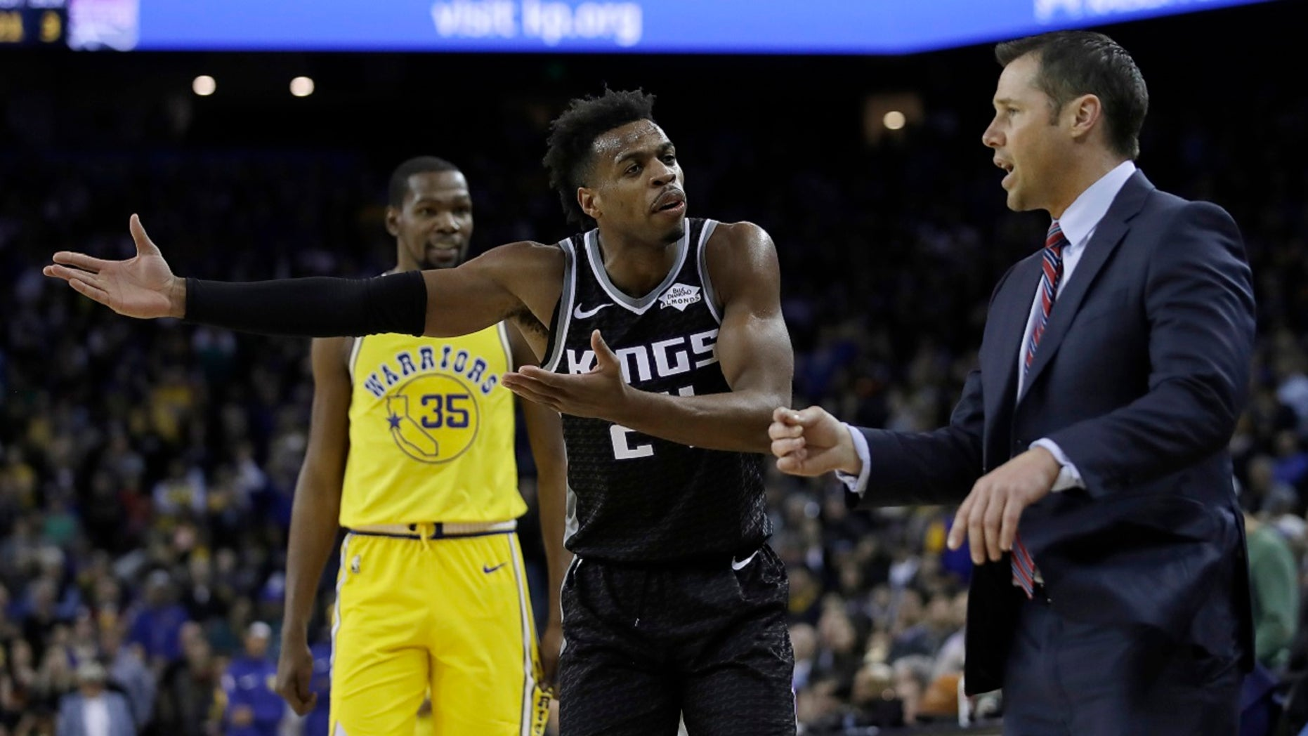 Sacramento Kings guard Buddy Hield, center, gestures to coach Dave Joerger, right, during the second half of the team's NBA basketball game against the Golden State Warriors on Thursday, Feb. 21, 2019, in Oakland, Calif.