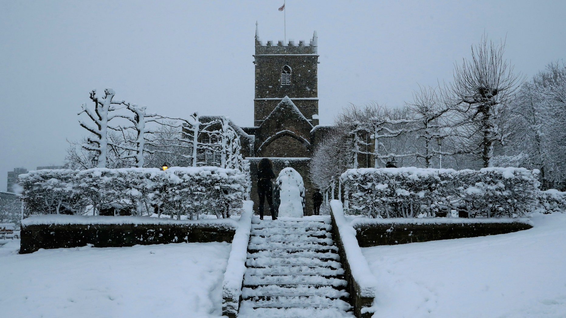 FILE - In this file photo dated Friday, Feb. 1, 2019, snow falls over St Peter's Church in Bristol, southwest England. The Church of England's governing Synod on Friday Feb. 22, 2019, lifted a 400-year-old rule requiring all churches to hold services every Sunday, acknowledging the reality of shrinking congregations and overworked priests. (AP Photo/Matt Dunham, FILE)