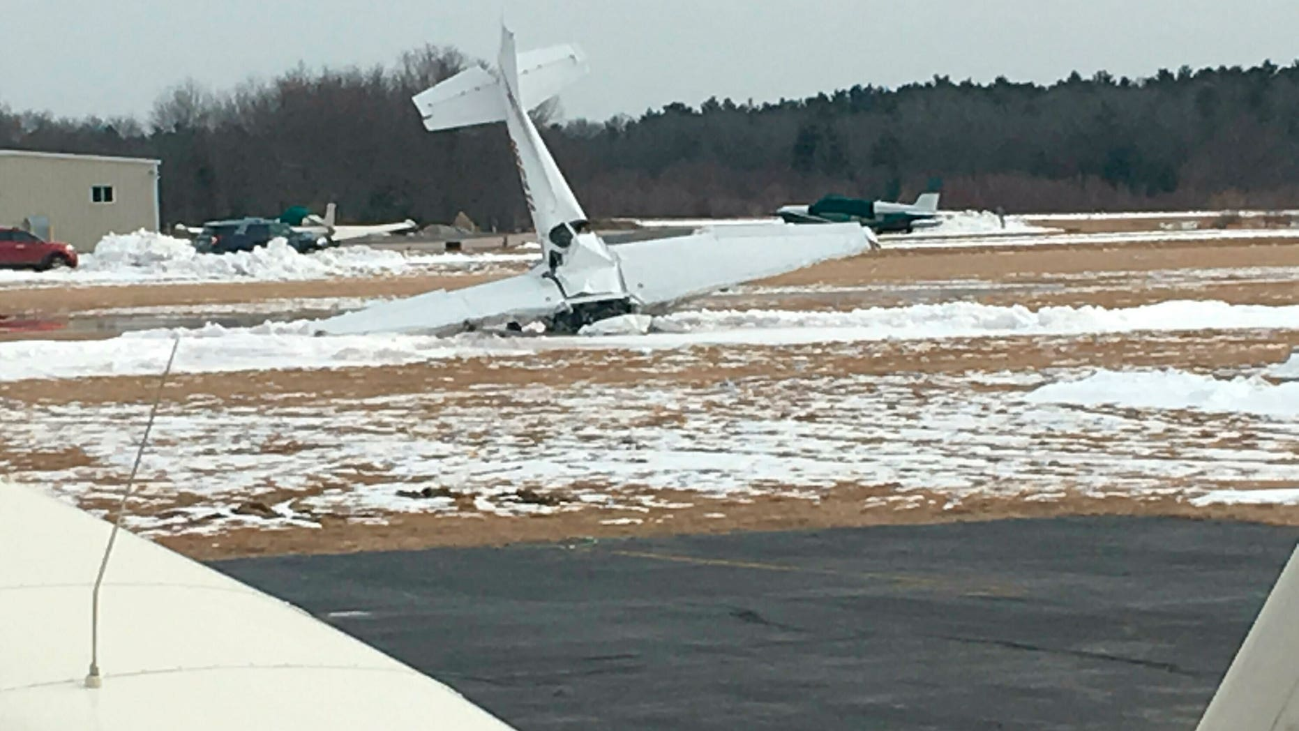 A small plane is seen resting on its nose following a crash and fire at Mansfield Municipal Airport in Mansfield, Mass., on Saturday. Massachusetts State Police confirmed that two people died in the crash, which occurred around 12:36 p.m.