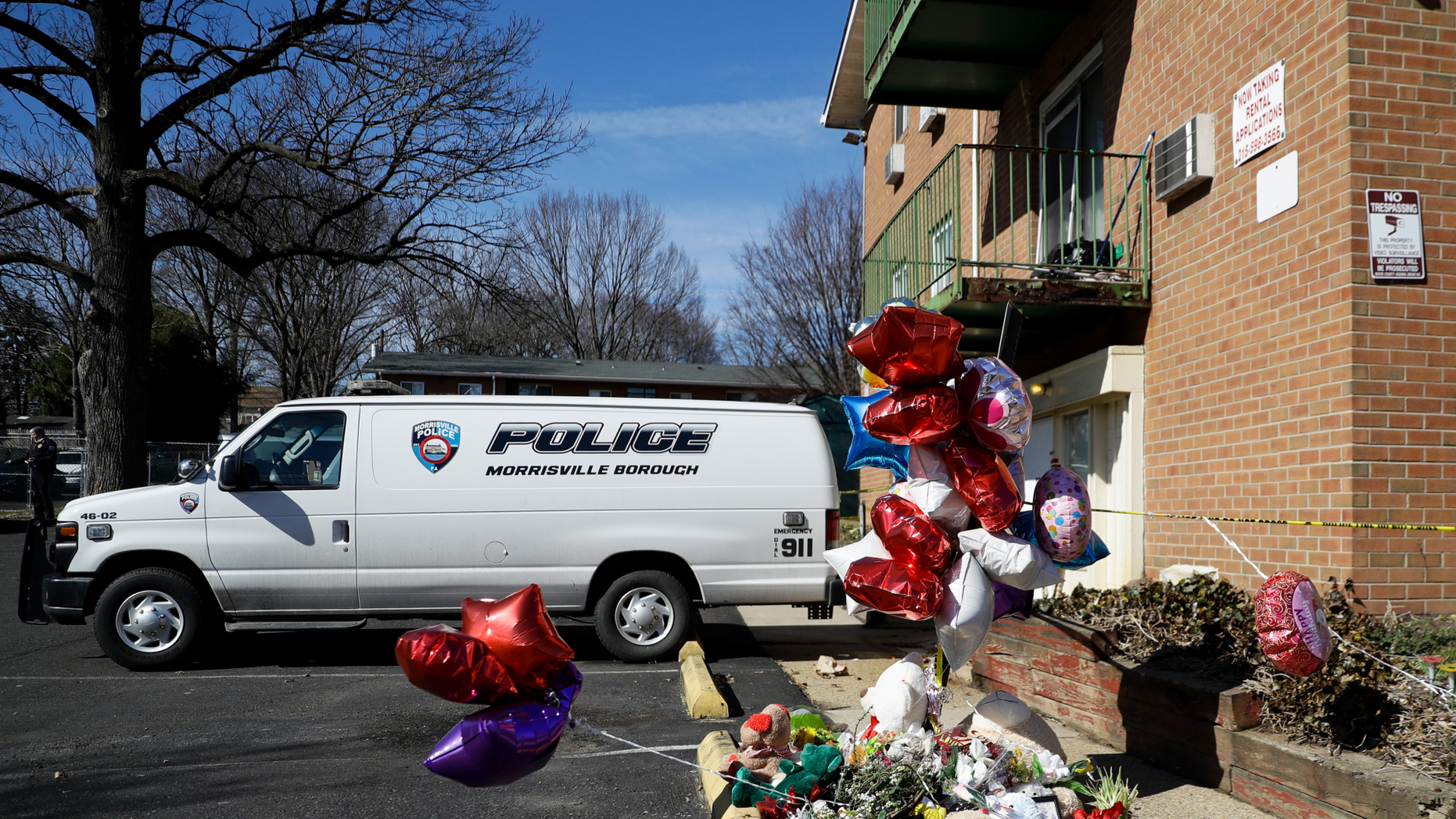 """A makeshift memorial is seen outside the Robert Morris Apartments, Thursday, Feb. 28, 2019, in Morrisville, Pa. A mother and her adult daughter killed five of their close relatives, including three children, and were found """"disoriented"""" after child welfare authorities arrived for a surprise visit to their trashed apartment outside Philadelphia, police and prosecutors said Tuesday. (AP Photo/Matt Slocum)"""