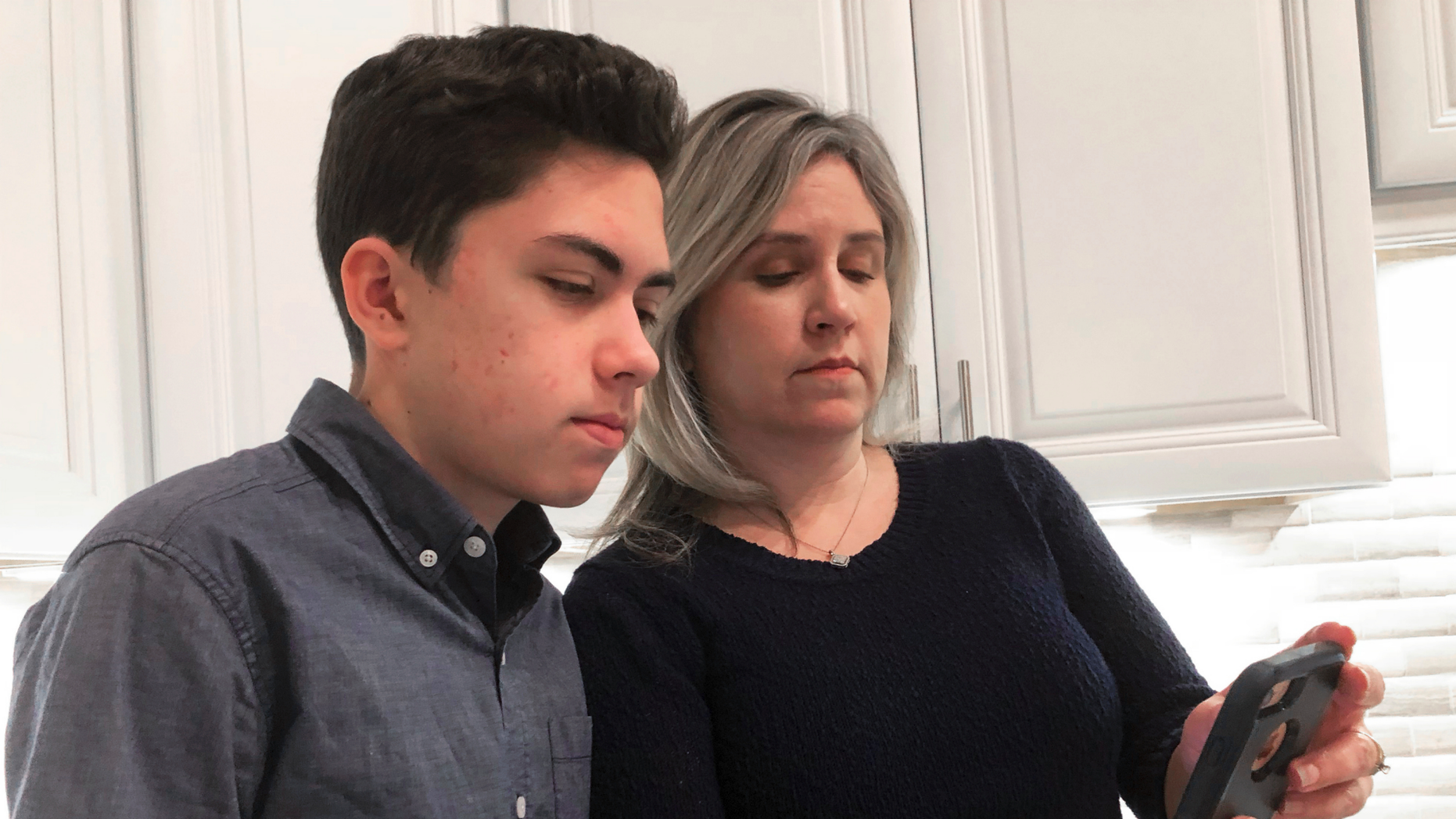 Grant Thompson and his mother, Michele, look at an iPhone in the family's kitchen in Tucson, Ariz., on Thursday, Jan. 31, 2019. (AP Photo/Brian Skoloff)