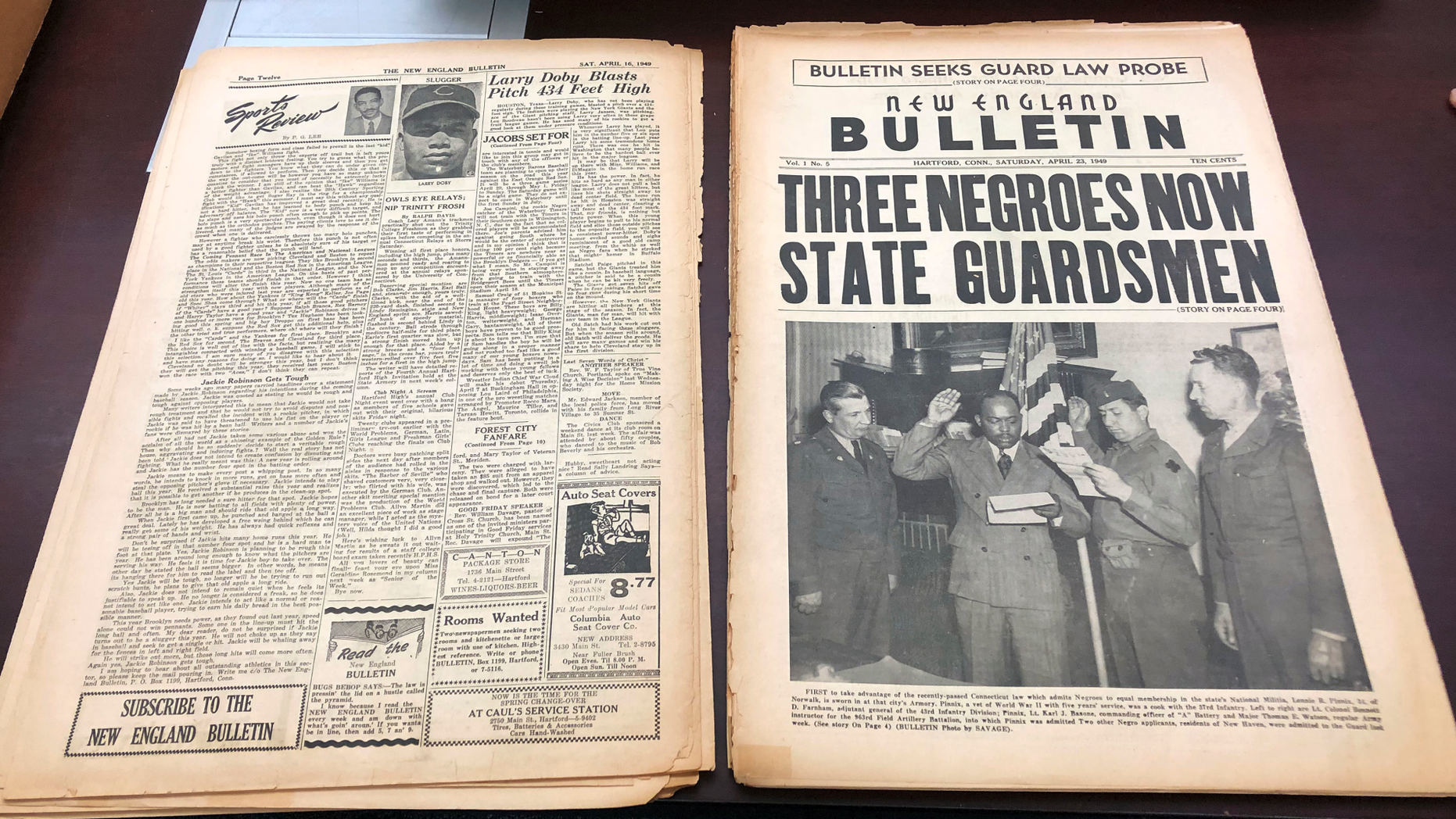 This Nov. 29, 2018 photo shows an original April 23, 1949 copy of the New England Bulletin, a black-owned and operated weekly newspaper in Hartford, Conn. Old microfilm of this and other incarnations of the newspaper are being digitized so they can be available online as part of the United States Newspaper Program. This issue highlights the first person to take advantage of a Connecticut law that granted blacks equal membership to the Connecticut National Guard. (AP Photo/Susan Haigh)