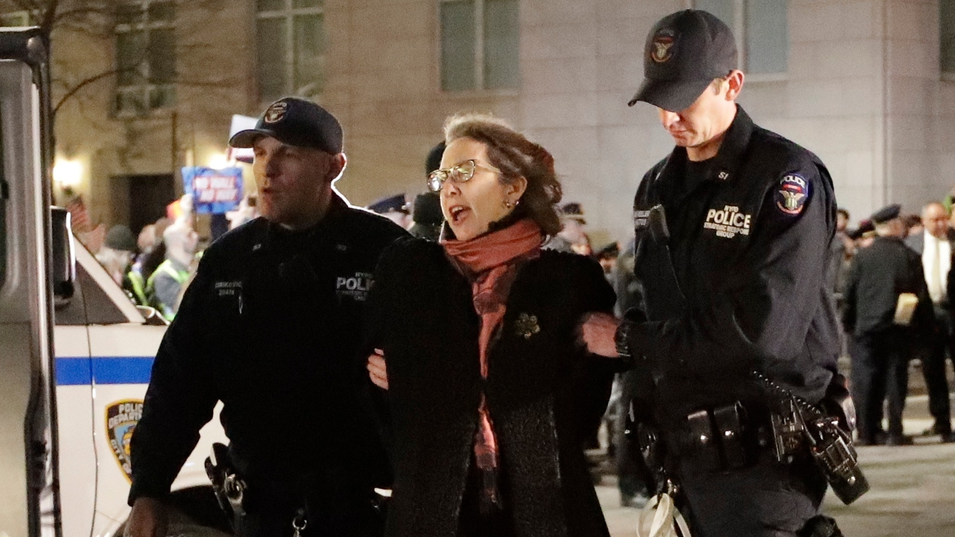 A protester is taken into custody outside Trump International Hotel & Tower on Friday, Feb. 15, 2019, in New York. Some people have been arrested while protesting President Donald Trump's national emergency declaration. The NYPD wasn't immediately able to say how many people were taken into custody outside the hotel. (AP Photo/Frank Franklin II)