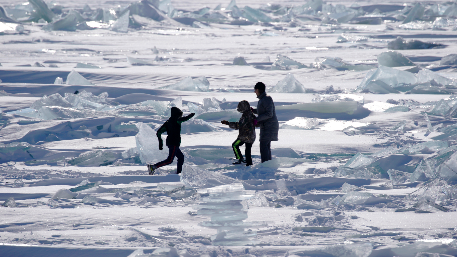 In this Friday, Feb. 22, 2019, photo, people play on the Ice on Lake Superior, starting to pack in along the shore near Duluth, Minn., and attracting explorers and ice fishermen out on to the lake. Access to the mainland ice caves remain CLOSED. Ice continues to move around quite a bit. Over the last few days, open water has been visible from Meyers Beach as well as near Eagle Island. This ice is typically poor quality ice, which reacts poorly to movement due to weak bonding along the fractures. (Brian Peterson/Star Tribune via AP)