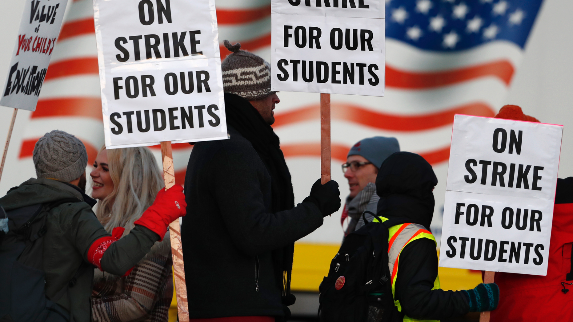 Teachers carry placards as they walk a picket line outside South High School early Monday, Feb. 11, 2019, in Denver. The strike on Monday is the first for teachers in Colorado in 25 years after failed negotiations with the school district over base pay. (AP Photo/David Zalubowski)