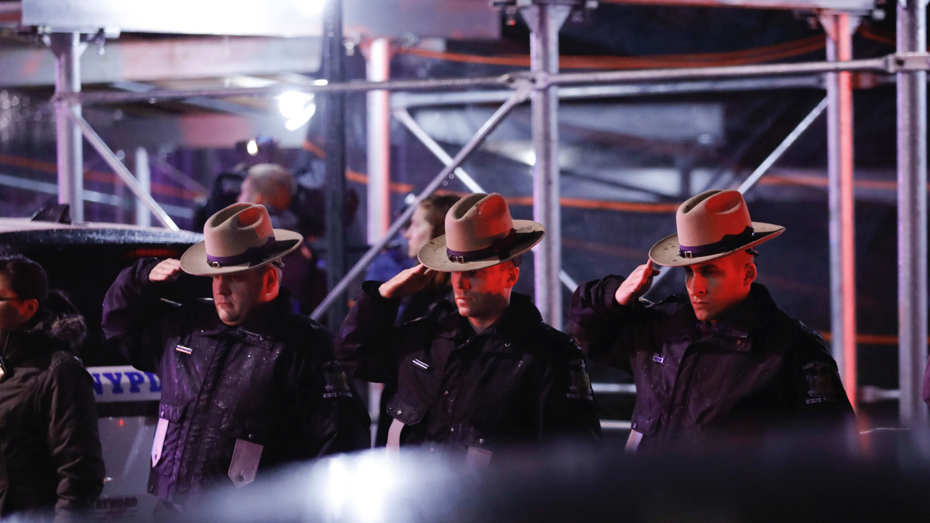 Officers salute a procession as the remains of slain Detective Brian Simonsen are removed from Jamaica Hospital Medical Center Tuesday, Feb. 12, 2019, in the Queens borough of New York. The NYPD detective and a NYPD sergeant were shot while responding to an armed robbery at a T-Mobile store in Queens. (AP Photo/Kevin Hagen)