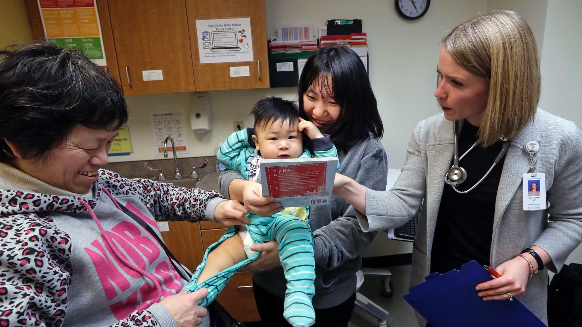 CORRECTS SPELLING OF ABEL, NOT ABLE - As his mother Wenyi Zhang holds him, one-year-old Abel Zhang looks at the book being given him by Dr. Lauren Lawler, right, as his grandmother Ding Hong helps with his clothes moments after the child received the last of three inoculations, including a vaccine for measles, mumps, and rubella (MMR), at the International Community Health Services Wednesday, Feb. 13, 2019, in Seattle. A recent measles outbreak has sickened dozens of people in the Pacific Northwest, most in Washington state and, of those, most are concentrated in Clark County, just north of Portland, Oregon. Washington Gov. Jay Inslee declared a state of emergency over the outbreak last month. (AP Photo/Elaine Thompson)
