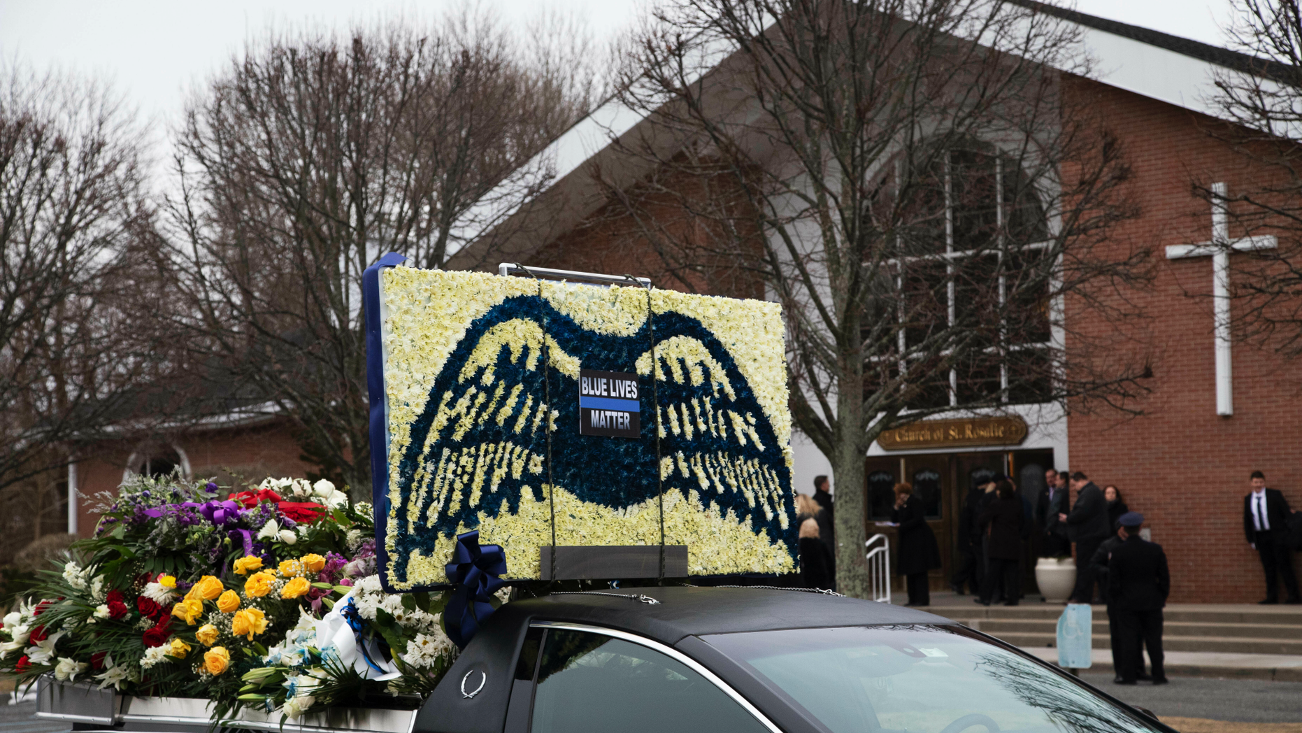 A limousine that is part of the funeral procession for Det. Brian Simonsen, is parked in front of the Church of St. Rosalie in Hampton Bays, N.Y., Wednesday, Feb. 20, 2019. Simonsen, with the New York City Police Department, was killed by friendly fire Feb. 12 as he and six other officers opened fire on a robbery suspect who police say was pointing at them what appeared to be a handgun. (AP Photo/Mark Lennihan)