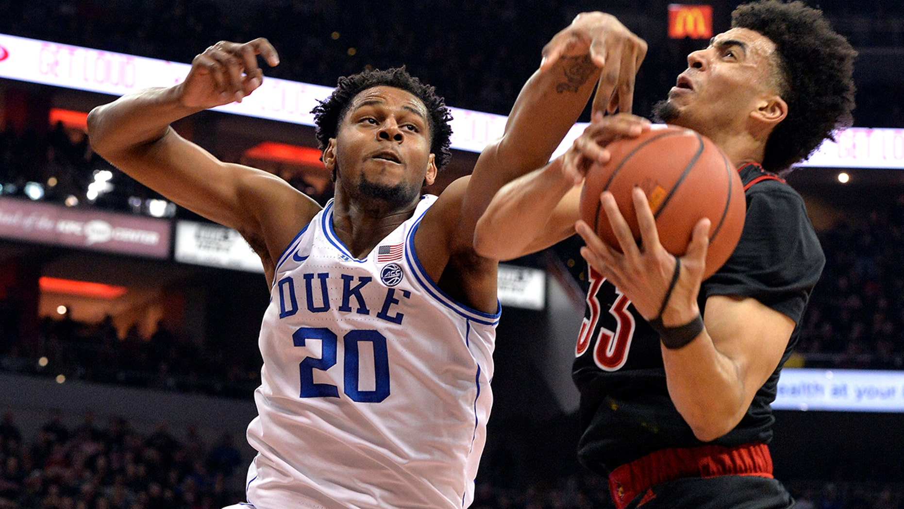 Duke center Marques Bolden (20) and Louisville striker Jordan Nwora (33) compete for a rebound during the first half of an NCAA college basketball game in Louisville, Kentucky, on Tuesday, February 12, 2019. ( Associated Press)