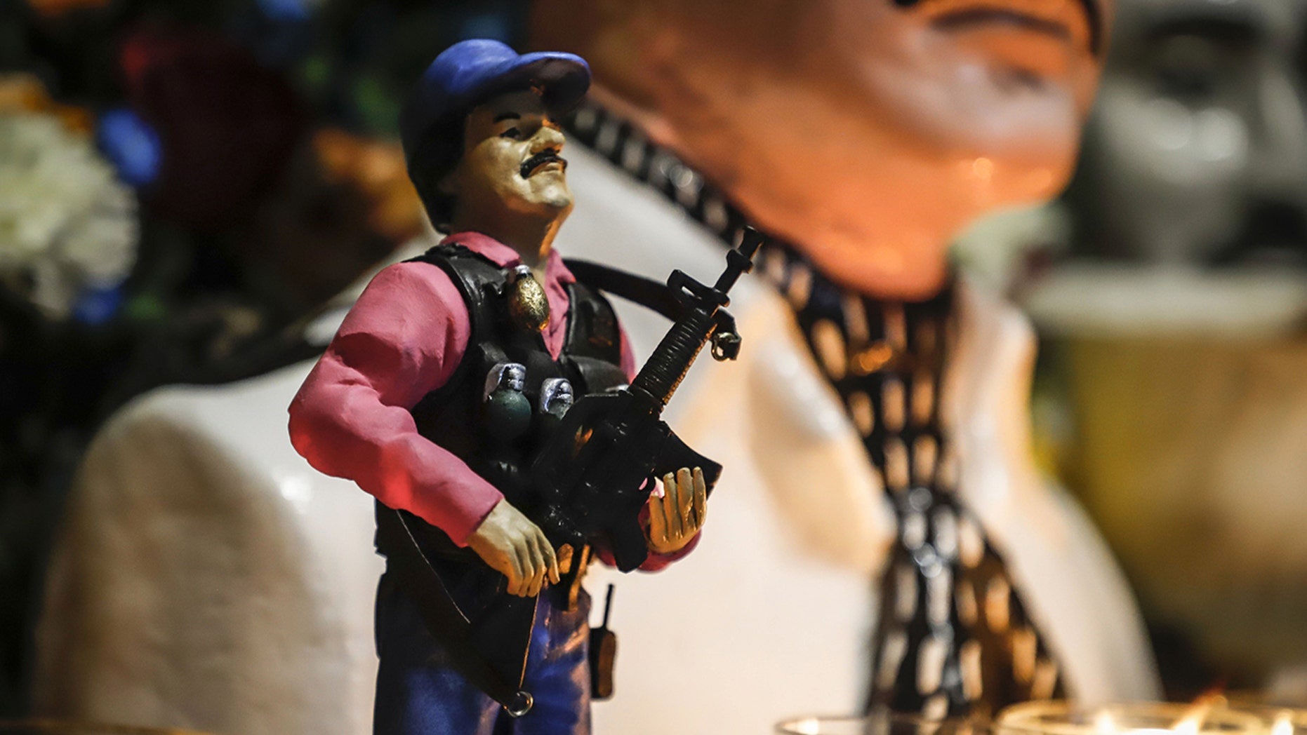 """A statue of Mexican drug lord Joaquin """"El Chapo"""" Guzman, is displayed for sale near a bust of narco-saint Jesus Malverde, at his chapel in Culiacan, Sinaloa state in northwest Mexico on Feb. 19. (Photo by RASHIDE FRIAS / AFP) (Photo credit should read RASHIDE FRIAS/AFP/Getty Images)"""