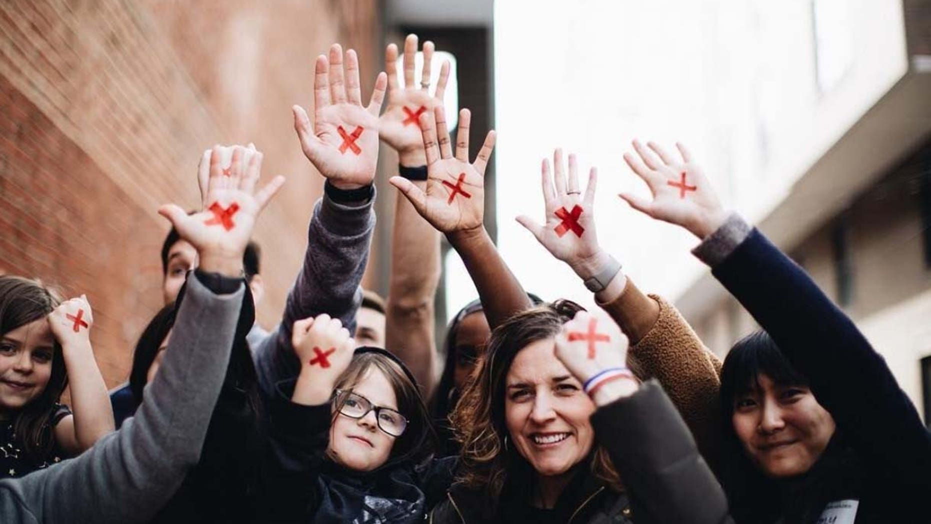 """People put a red X on their hand to raise awareness for the """"End It Movement,"""" in an effort to end modern-day slavery."""