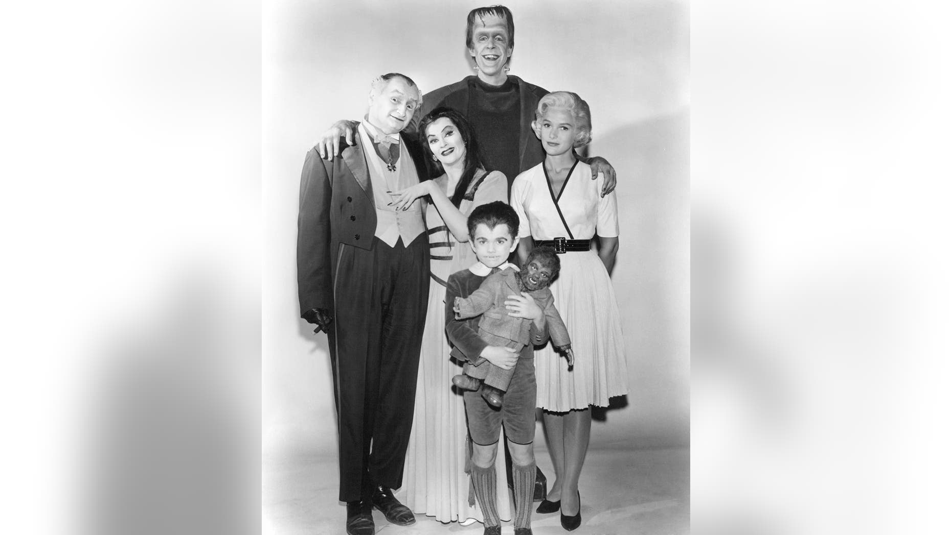"""Members of the Munster family in a publicity still for Season 1 of the comedy-horror TV series """"The Munsters.,"""" 1964. Left to right: Al Lewis (1923 - 2006) as Grandpa, Yvonne De Carlo as Lily Munster, Butch Patrick as Eddie Munster, Fred Gwynne as Herman Munster and Beverley Owen as Marilyn Munster."""