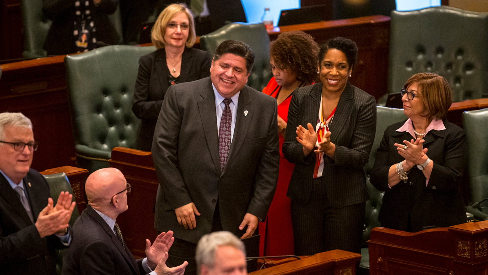 Illinois Gov. J.B. Pritzker, left, and Illinois Lt. Gov. Juliana Stratton, right, are acknowledged on the House floor at the Illinois State Capitol, Thursday, Feb. 14, 2019, in Springfield, Ill. Illinois legislators moved quickly to deliver one of Pritzker's top campaign promises, a gradual hike in the statewide minimum wage from $8.25 to $15 an hour, more than double the pay floor that most of its Midwestern neighbors require. (Justin L. Fowler/The State Journal-Register via AP)