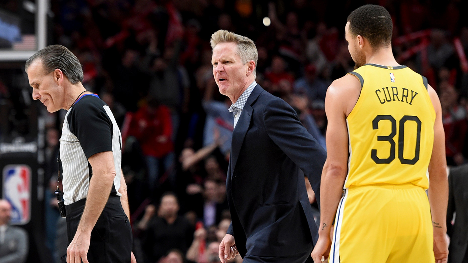 Golden State Warriors coach Steve Kerr, center, yells at referee Ken Mauer, left, after being called for a technical foul, while guard Stephen Curry, right, watches during the second half of an NBA basketball game against the Portland Trail Blazers in Portland, Ore., Wednesday, Feb. 13, 2019. The Blazers won 129-107.