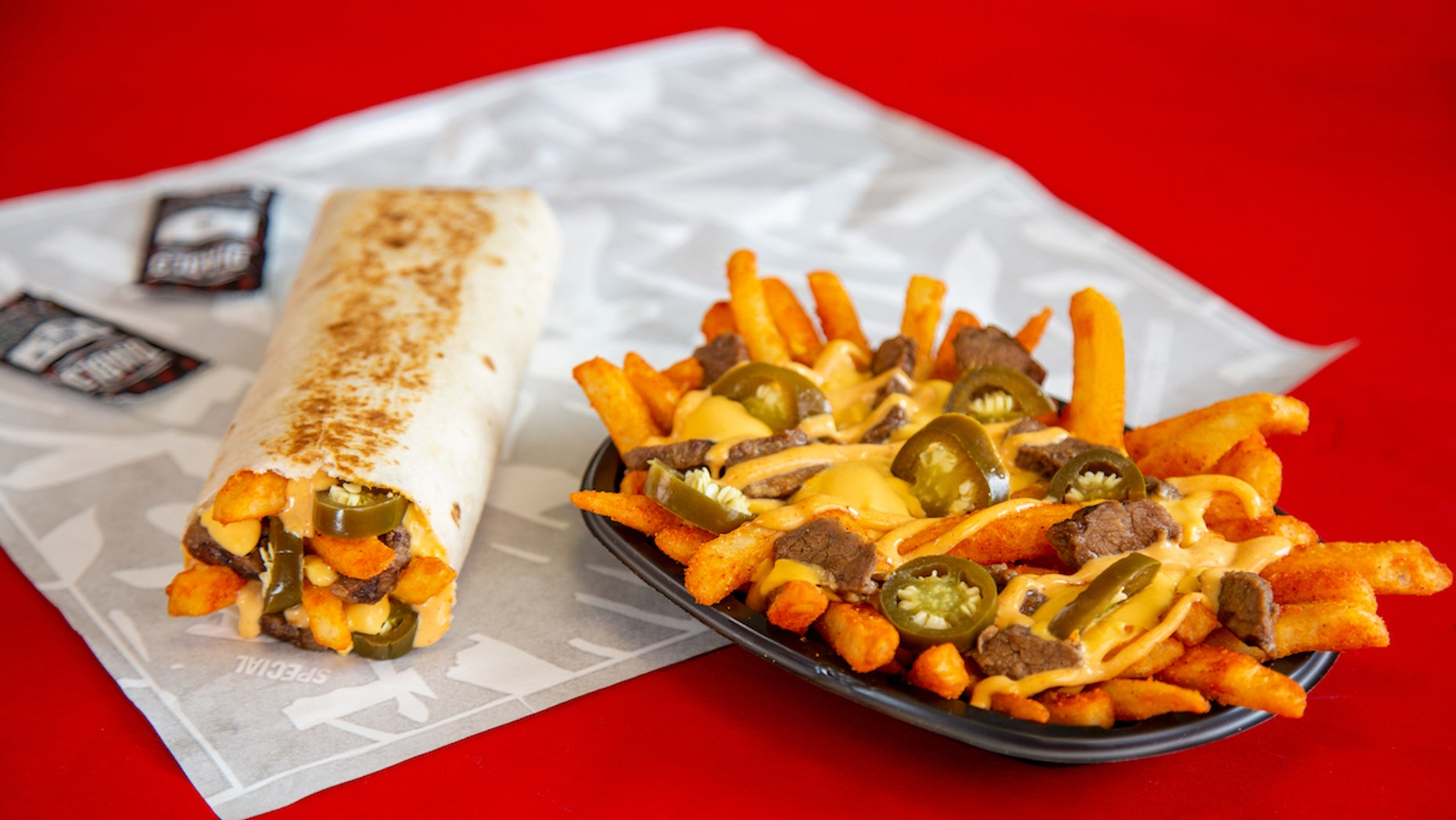 """Steak Rattlesnake Fries consist of a base of """"boldly"""" spicy seasoned fries, topped with marinated steak, nacho cheese sauce, creamy jalapeño sauce, and a ton of spicy cut up jalapeños.<br>"""