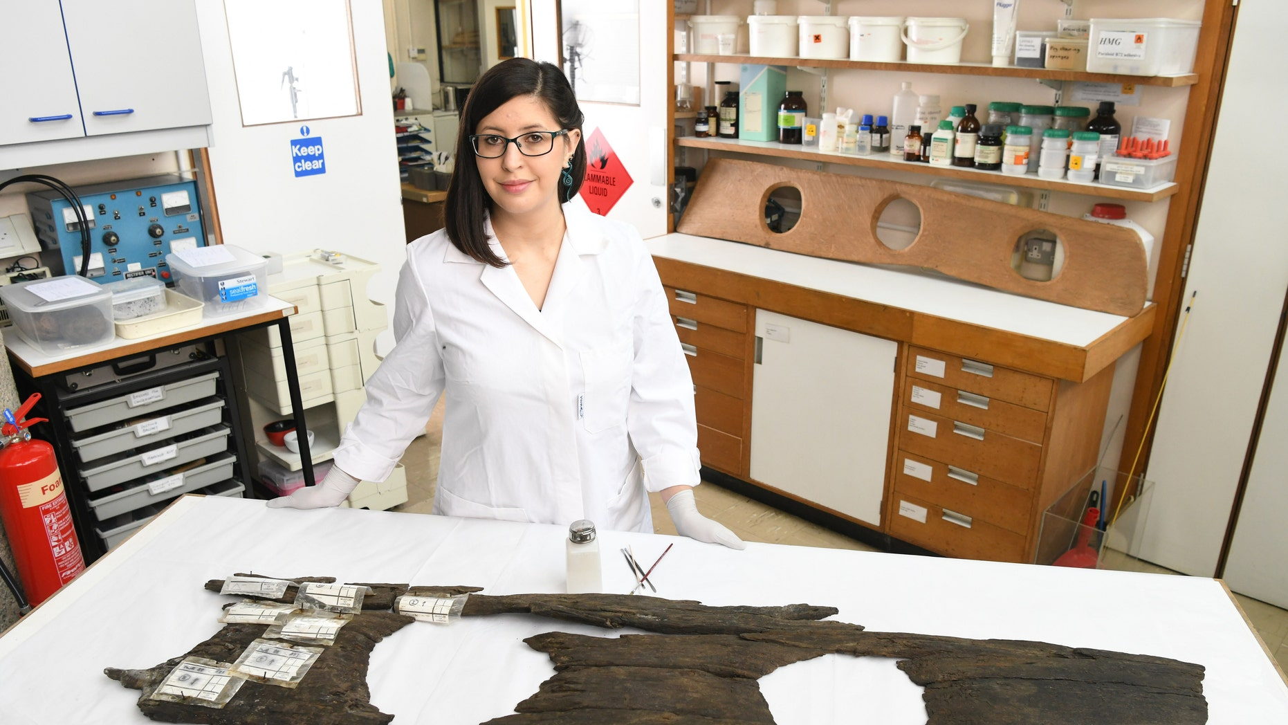 Conservator Luisa Duarte works on the 12th-century triple toilet seat, before it goes on display as part of the Museum of London Docklands Secret Rivers exhibition.