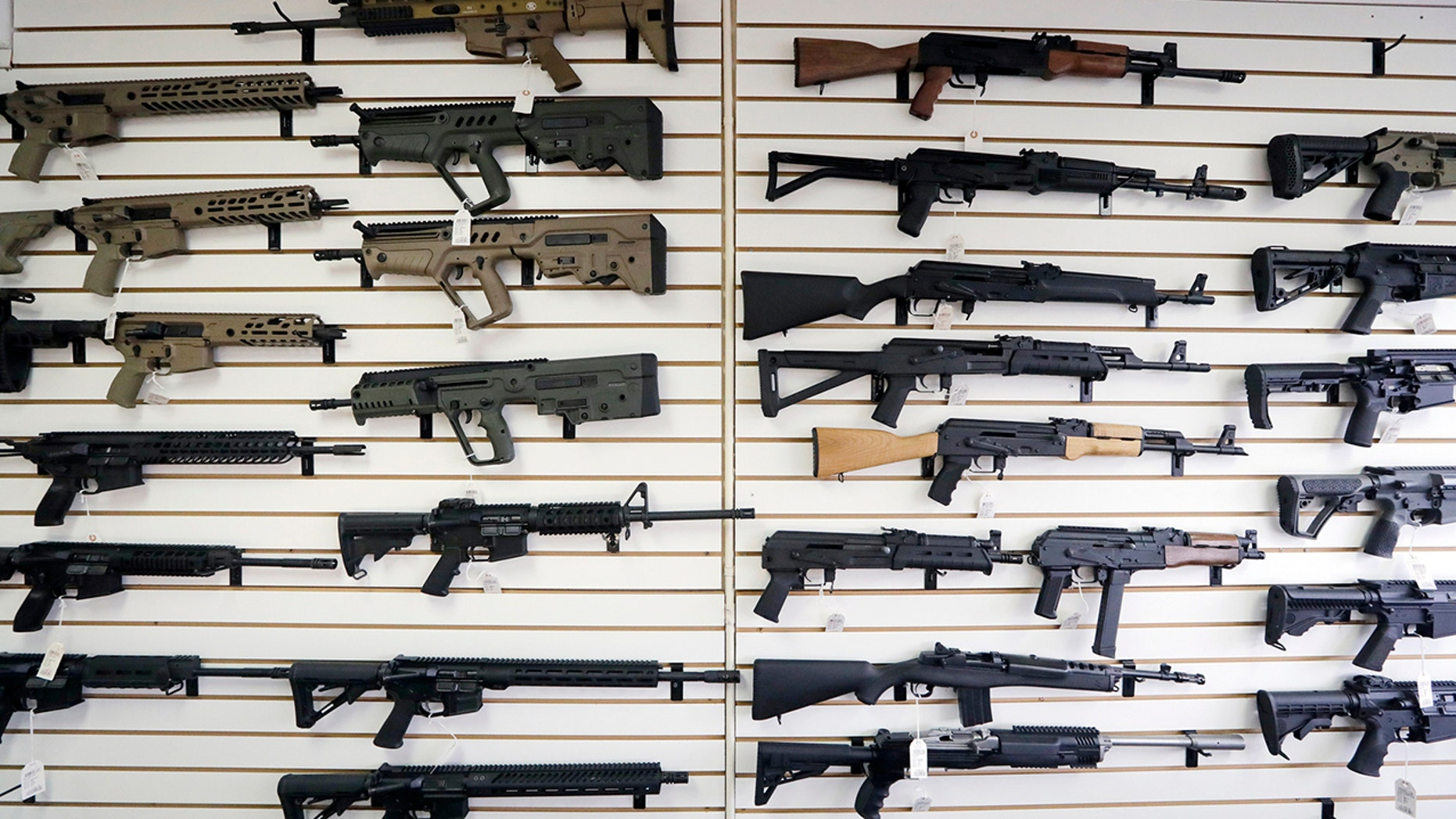 In this photo taken Oct. 2, 2018, semi-automatic rifles fill a wall at a gun shop in Lynnwood, Wash. (AP Photo/Elaine Thompson, File)