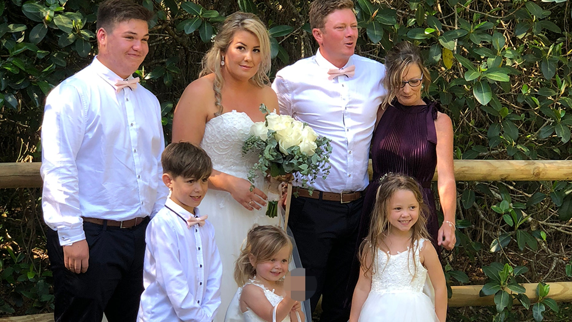 (Pictured: l-r Ashton,15, Tyler,8, Hannah,31, Maddison,3, Nathan,31. Halle,5, and mother in law Louise) - A mortified mom was left red-faced after her cheeky little girl hilariously popped the middle finger up during a family photoshoot on her wedding day.