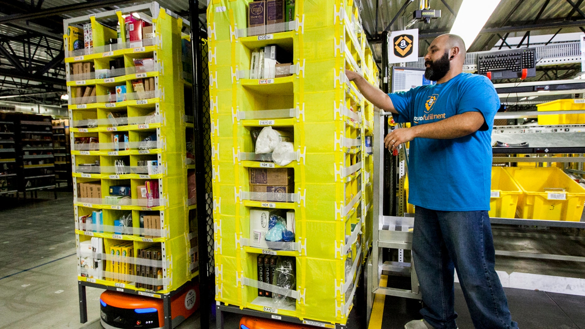 An Amazon fulfillment center employee is seen above, working with a robot.