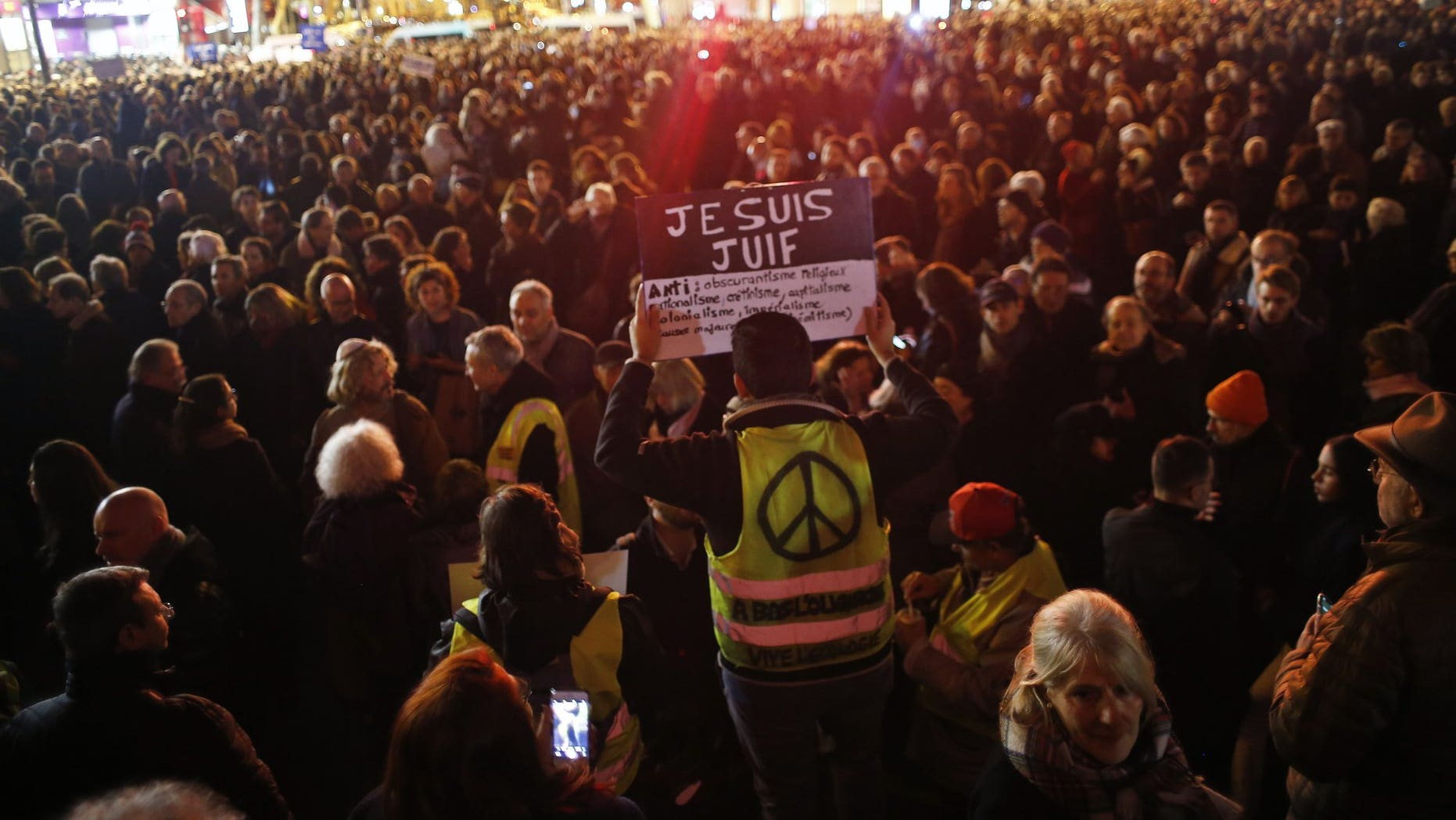 """A man wearing a yellow vest holds a placard reading """"I am jew"""", during a gathering at the Republique square to protest against anti-Semitism, in Paris, France, Tuesday, Feb. 19, 2019. In Paris and dozens of other French cities, ordinary citizens and officials across the political spectrum geared up Tuesday to march and rally against anti-Semitism, following a series of anti-Semitic acts that shocked the nation."""