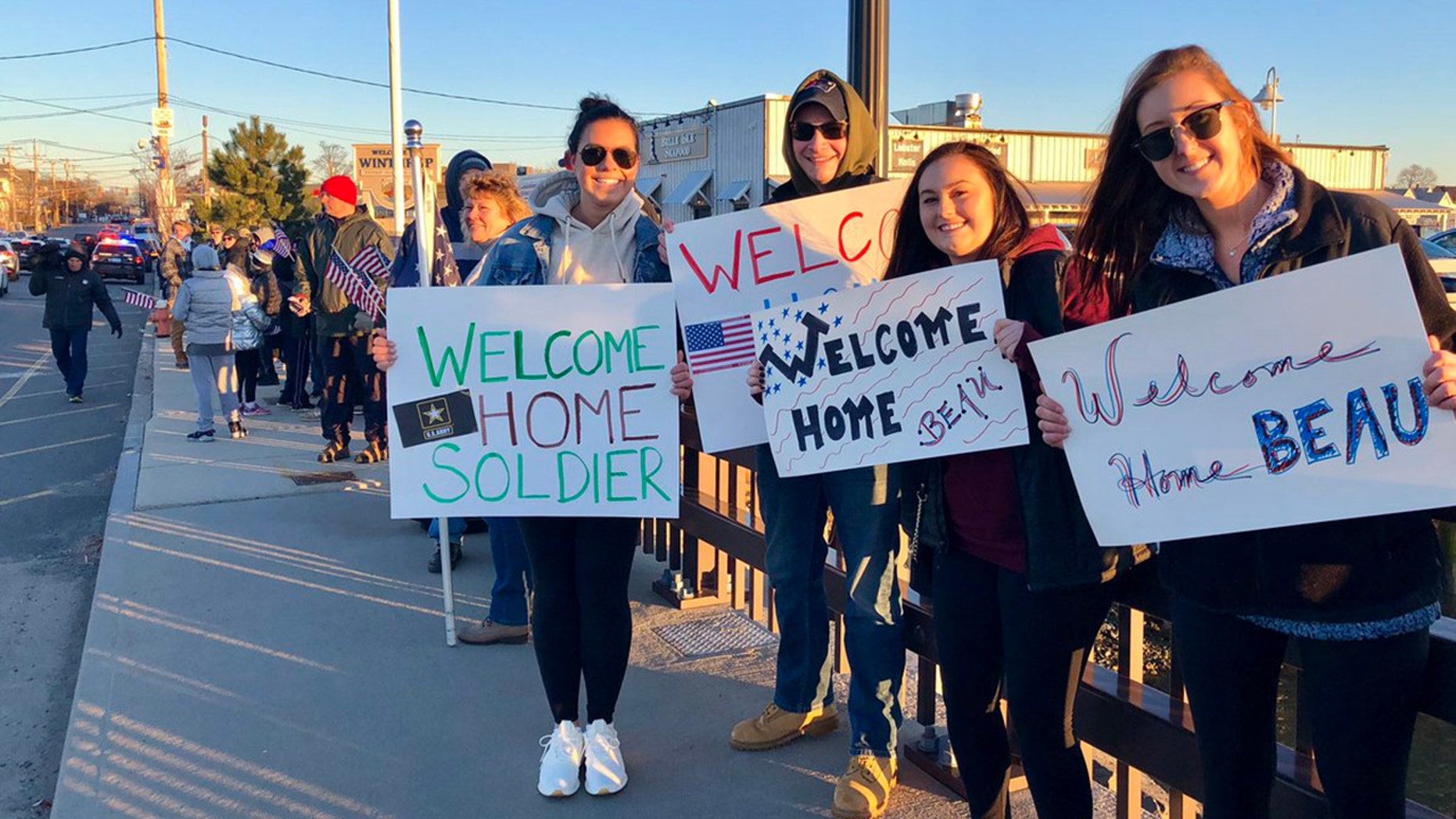 Dozens lined a bridge into Winthrop, Mass., Saturday to surprise U.S. Army soldier Beau Schlichting who returned home from a nine-month deployment in Afghanistan.