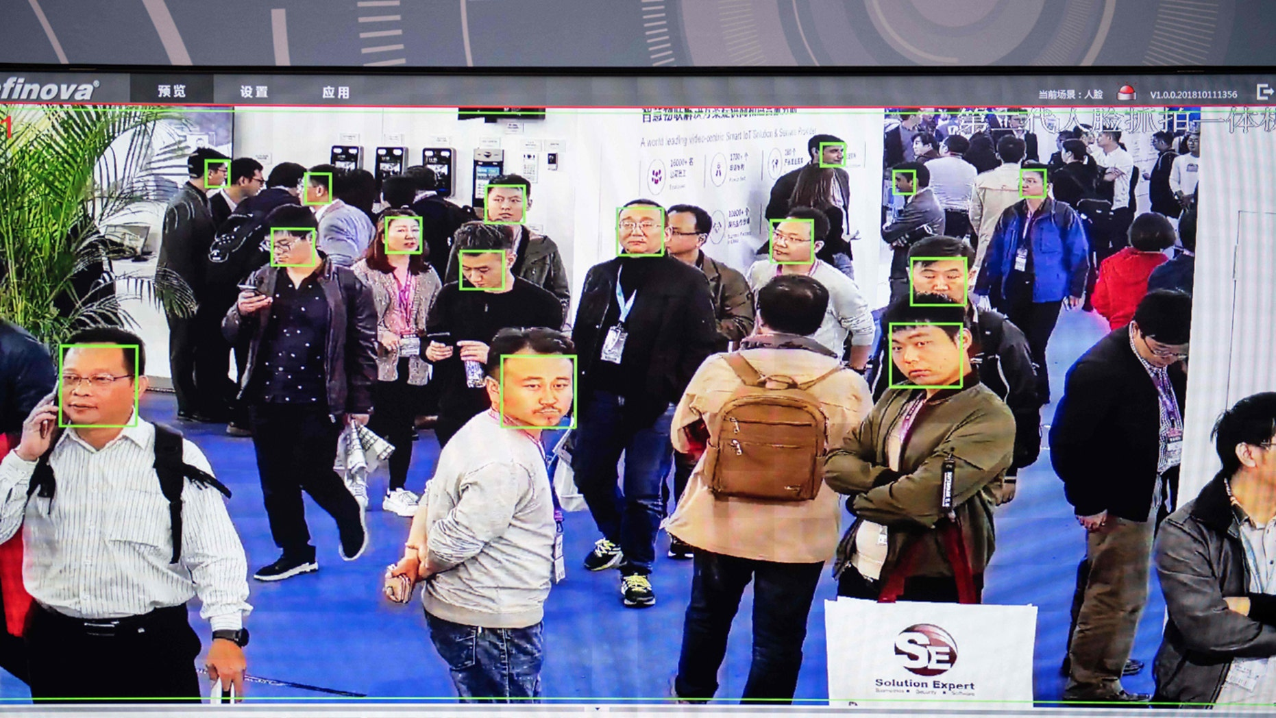 A screen shows visitors being filmed by AI (Artificial Intelligence) security cameras with facial recognition technology at the 14th China International Exhibition on Public Safety and Security at the China International Exhibition Center in Beijing on October 24, 2018.
