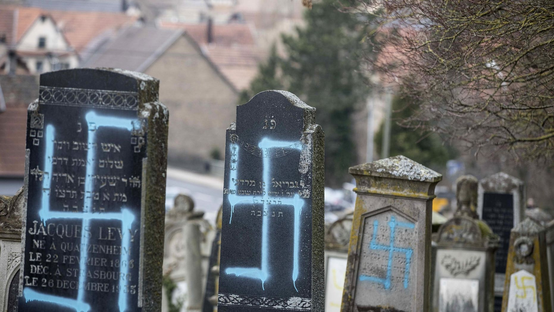 Vandalized tombs with tagged swastikas are pictured in the Jewish cemetery of Quatzenheim, eastern France, Tuesday, Feb.19, 2019. Marches and gatherings against anti-Semitism are taking place across France following a series of anti-Semitic acts that shocked the country.