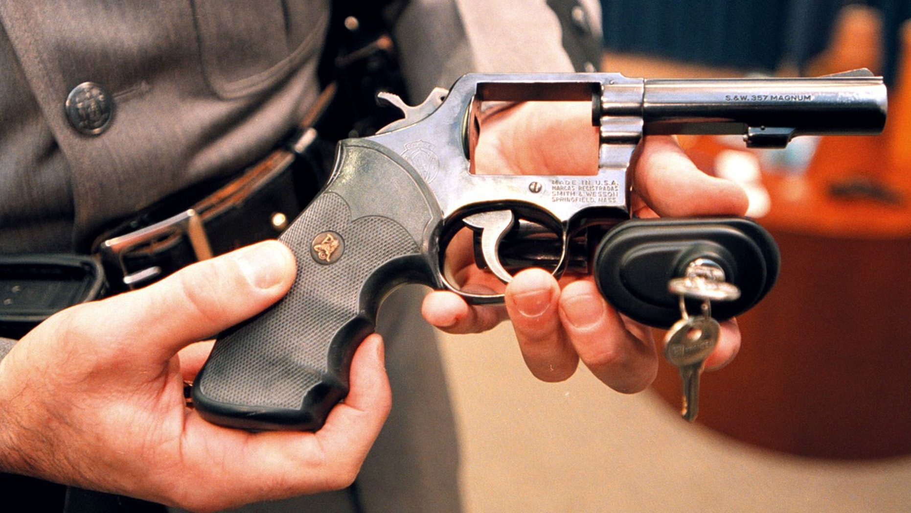 A New York State police officer displays a handgun with a child safety lock on March 15, 2000.