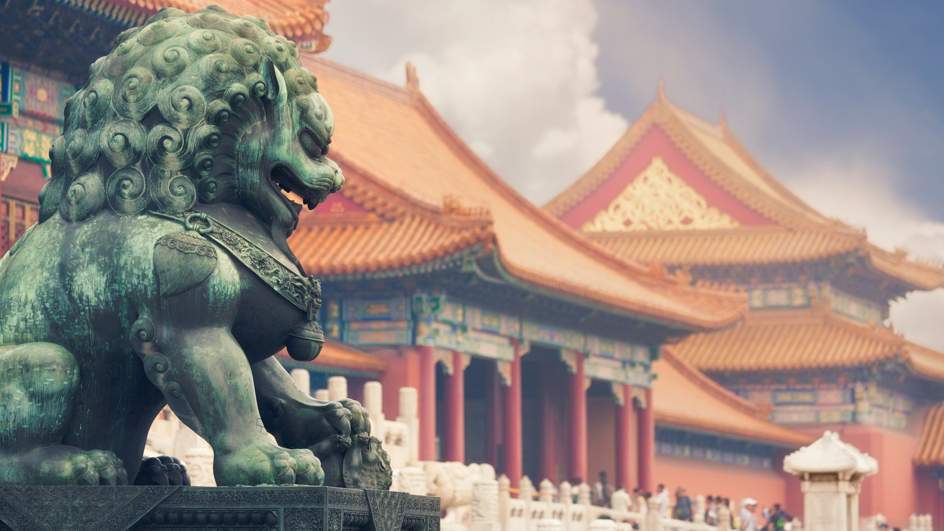 An old imperial lion sculpture in seen in front of historical Forbidden City buildings.