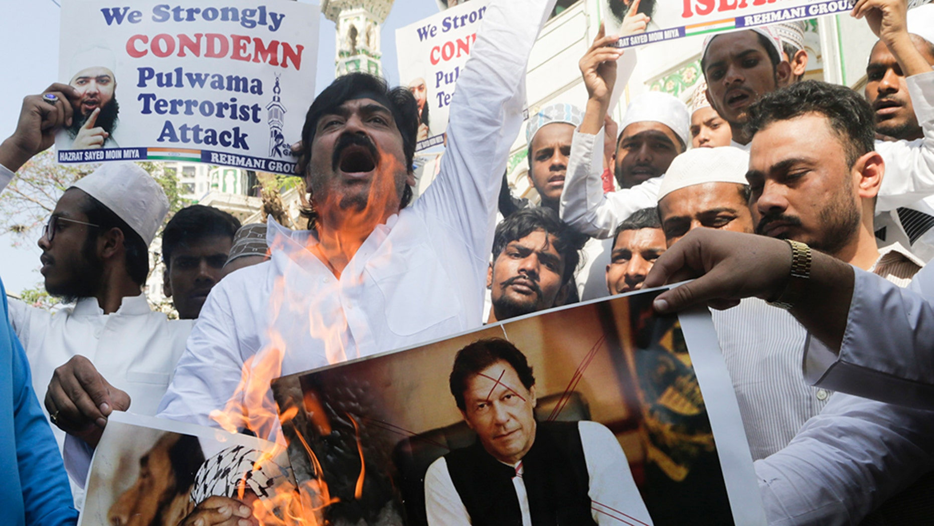 Indian Muslims burn posters of Pakistani prime minister Imran Khan, center, and Jaish-e-Mohammed leader Masood Azhar, during a protest against Thursday's attack on a paramilitary convoy in Kashmir that killed at least 40, in Mumbai, India, Friday.